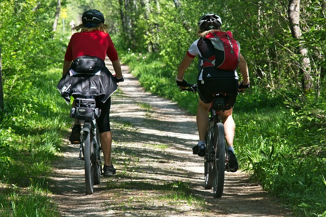 Dva lidé, kteří jedou po lesní cestě na kolech