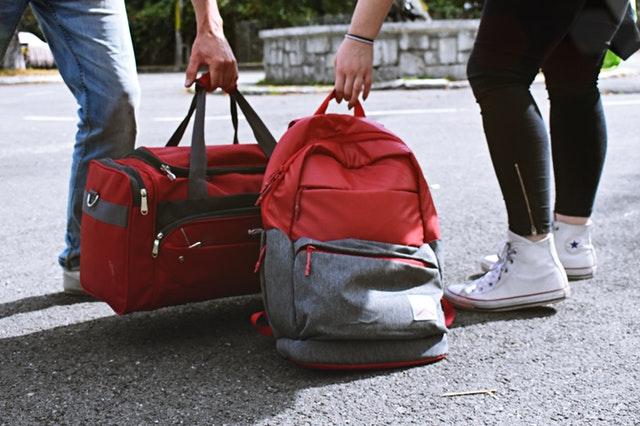 Muž a žena beroucí ze země cestovní tašky